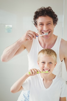 Portrait of father and son brushing teeth