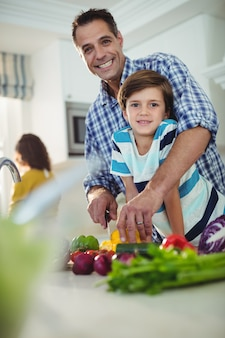 Portrait of father and son chopping vegetables in kitchen