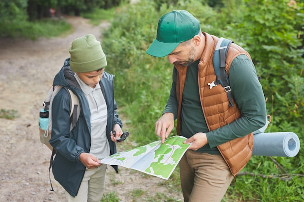 Portrait of father and son hiking together and looking at map while exploring paths in forest