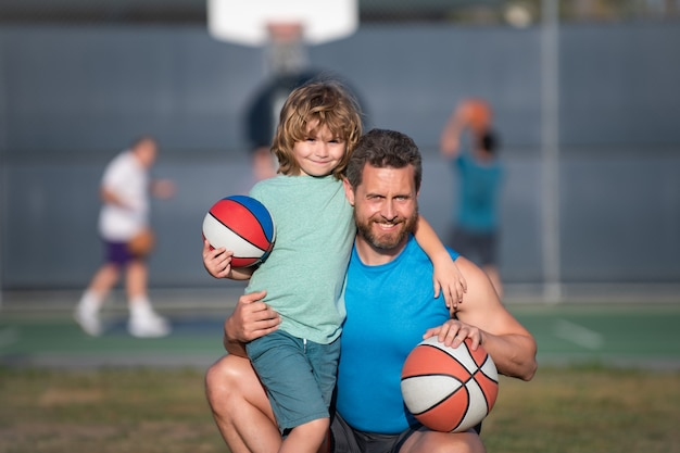 Portrait of father and son playing basketball