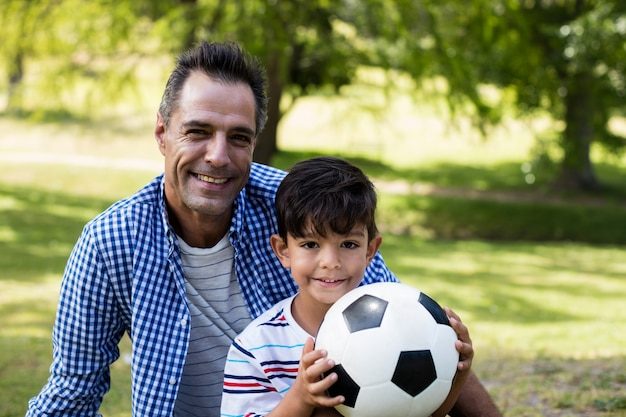 Portrait of father and son sitting in park