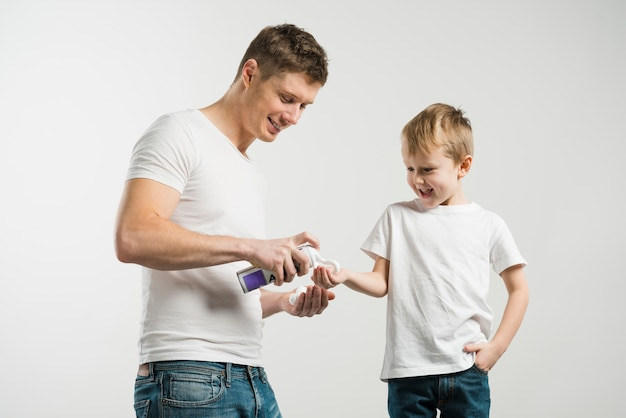 Portrait of a father spraying shaving foam on his son's hand against white backdrop