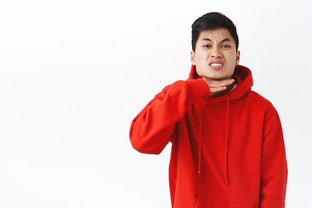 Ritratto di un ragazzo asiatico stufo e incazzato che è arrabbiato, infastidito con qualcuno, che mostra il gesto della gola tagliata come se avesse abbastanza testa di stronzate, malato e stanco della persona che dice bugie, in piedi sul muro bianco.