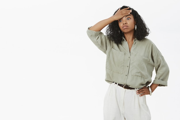Portrait of fed up tensed and exhausted cute dark-skinned businesswoman in blouse and pants holding hand on waist exhaling