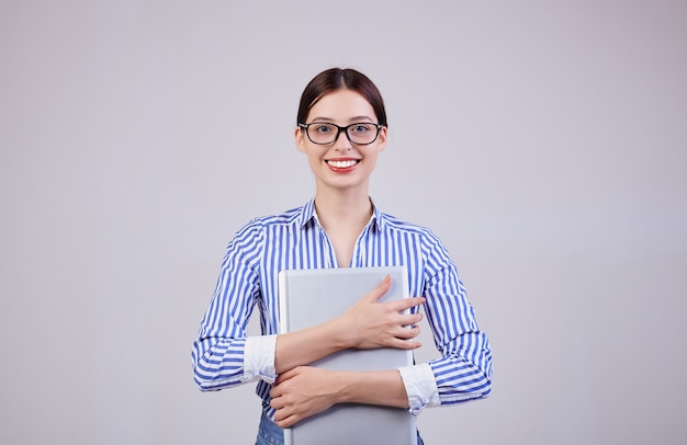 Portrait of a female administrator in a striped white-blue shirt with glasses and a laptop on gray. employee of the year, business lady. busy woman.