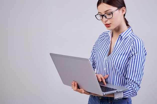 Portrait of a female administrator in a striped white-blue shirt with glasses and a laptop on gray. employee of the year. hard working woman every day.