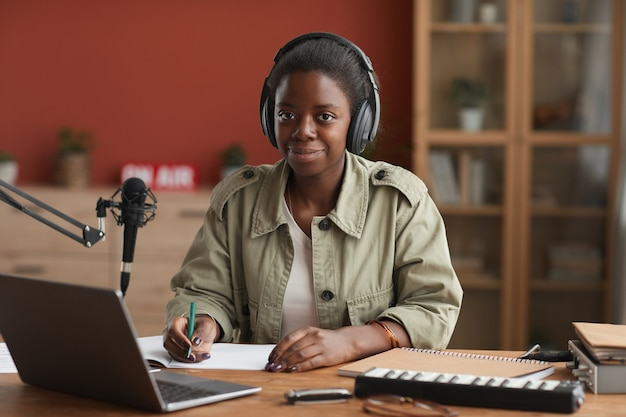 Portrait of female african-american musician looking at camera while composing at home, copy space