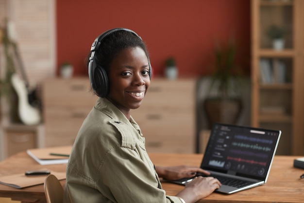 Portrait of female african-american musician using laptop and smiling at camera while composing music at home recording studio, copy space