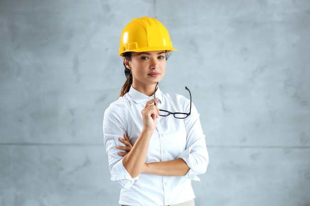 Portrait of female architect with helmet on head standing and looking at camera.