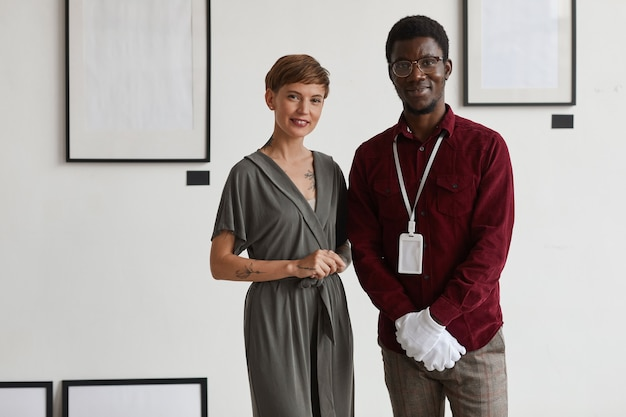 Portrait of female art gallery manager posing with african-american worker while standing against white wall and smiling at camera,