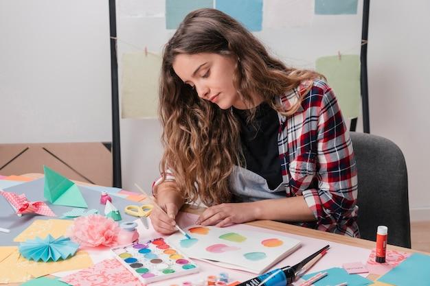 Portrait of female artist painting on white paper