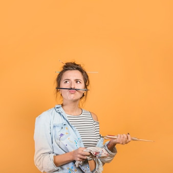 Portrait of female artist with paintbrushes