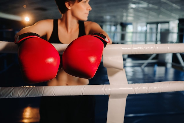Portrait of a female boxer in red gloves in the gym during training.