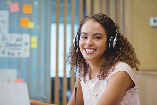 Portrait of female business executive listening music on headphone