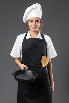 Portrait female chef with pan