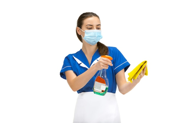 Portrait of female cleaning worker in whiteblue uniform and protective face mask isolated over