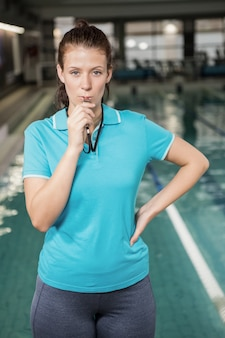 Portrait of female coach blowing a whistle