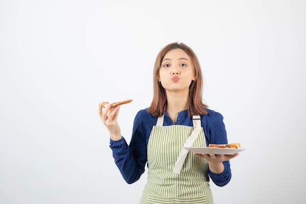 Ritratto di cuoca in grembiule che tiene pizza su bianco