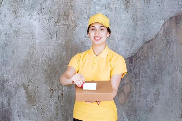 Portrait of female courier holding card with cardboard box