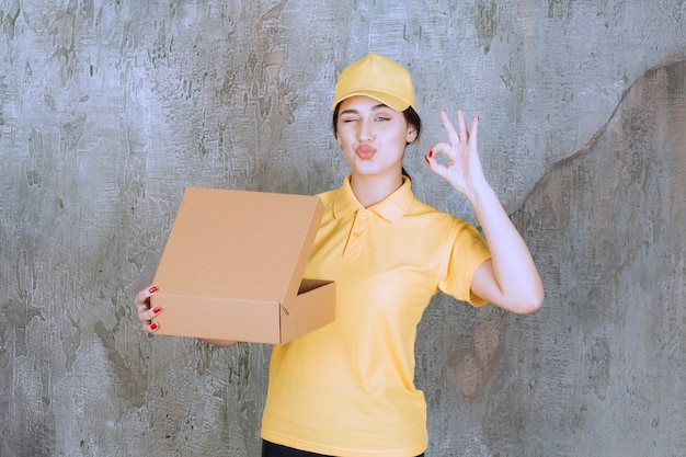 Portrait of female courier holding cardboard box and doing ok sign