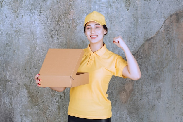 Portrait of female courier holding cardboard box and raising hand