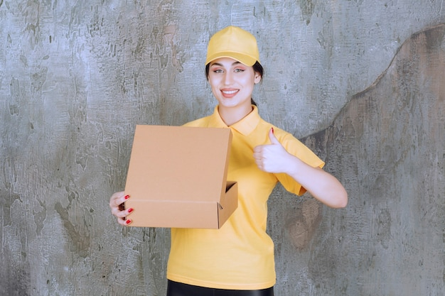 Portrait of female courier holding cardboard box and showing thumb up