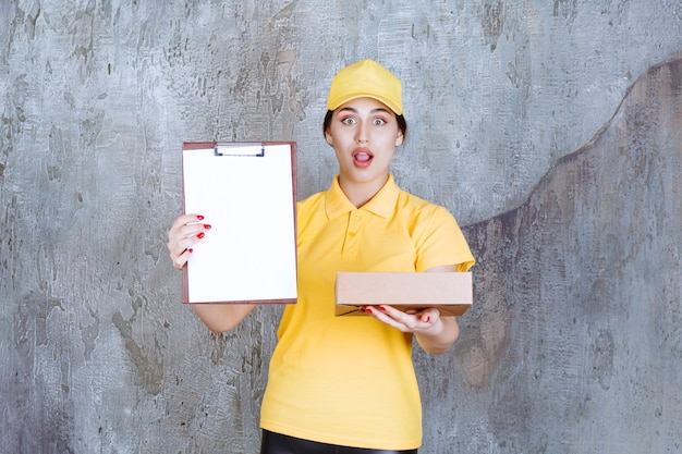 Portrait of female courier holding clipboard with cardboard box