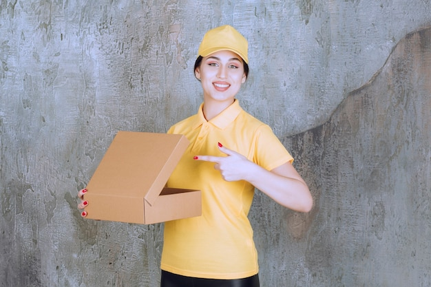 Portrait of female courier pointing at cardboard box