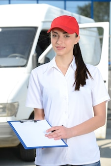 Portrait of female delivery driver with clipboard and box.