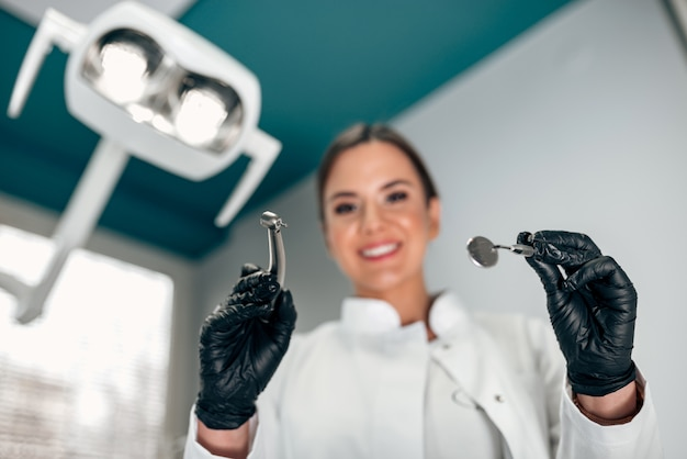 Portrait of a female dentist with dental tools from a patient's point of view.