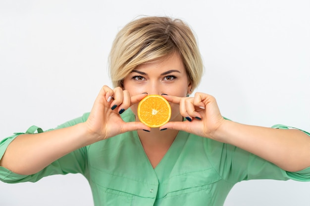 Portrait of female dietitian holding and showing a slice of orange on a white background