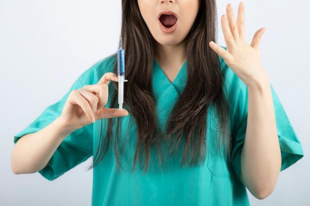 Ritratto di medico femminile che tiene una grande siringa. .
