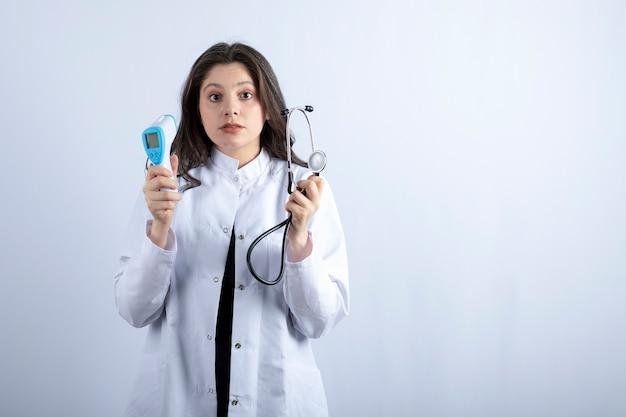 Ritratto di medico femminile che tiene termometro e stetoscopio sulla parete bianca.