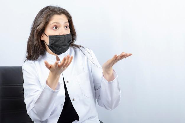 Ritratto di dottoressa in maschera medica e camice bianco che discute con qualcuno.