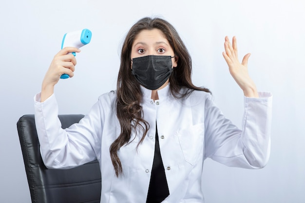 Portrait of female doctor in medical mask and white coat holding thermometer.