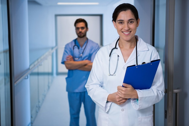 Portrait of female doctor standing with nurse in background