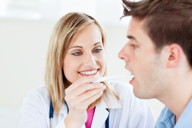 Portrait of a female doctor taking a saliva sample of a male patient with cottonbud