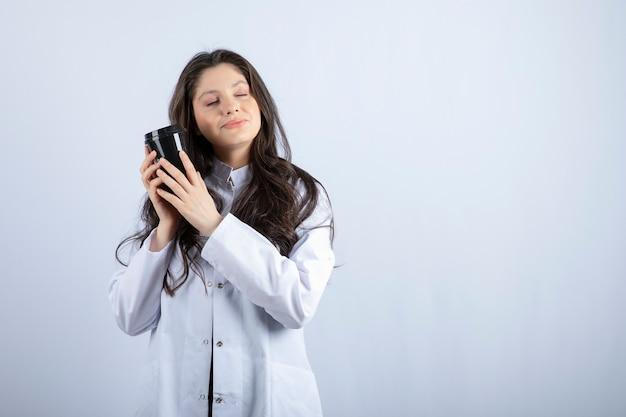Ritratto di donna medico con una tazza di caffè che dorme sul muro bianco.
