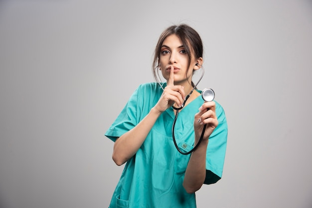 Portrait of female doctor with stethoscope on gray