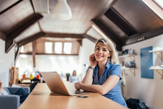 Portrait of a female entrepreneur in front of laptop in open space coworking office.
