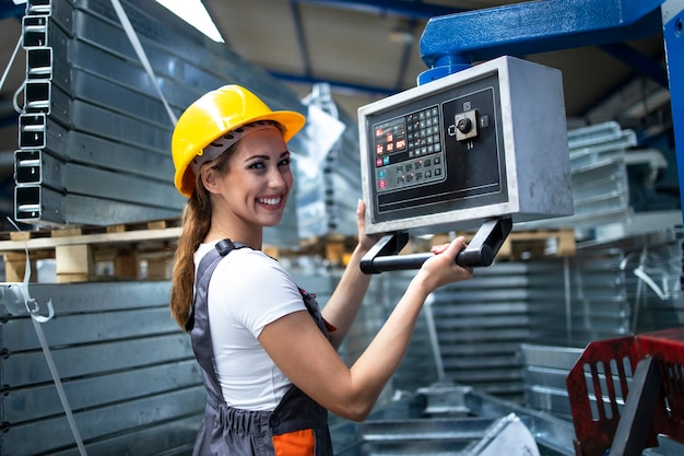 Ritratto di operaio femminile operante macchina industriale e impostazione dei parametri sul computer