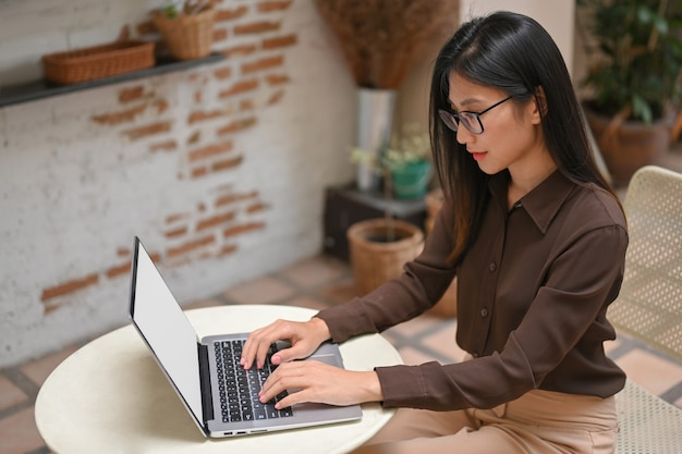 Portrait of female freelancer working with laptop on round table in coffee shop