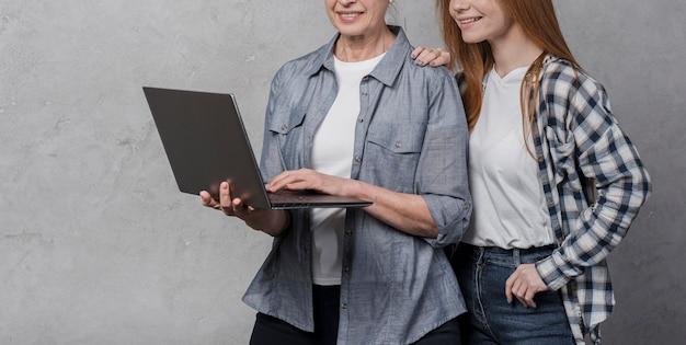 Portrait of female friends browsing a laptop
