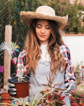 Portrait of a female gardener holding potted cactus plant