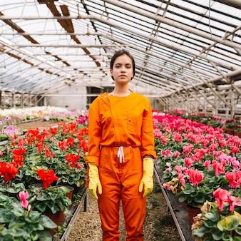 Portrait of a female gardener standing in greenhouse