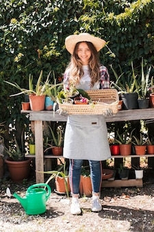 Portrait of a female gardener wearing hat holding the selected potted plant in the basket