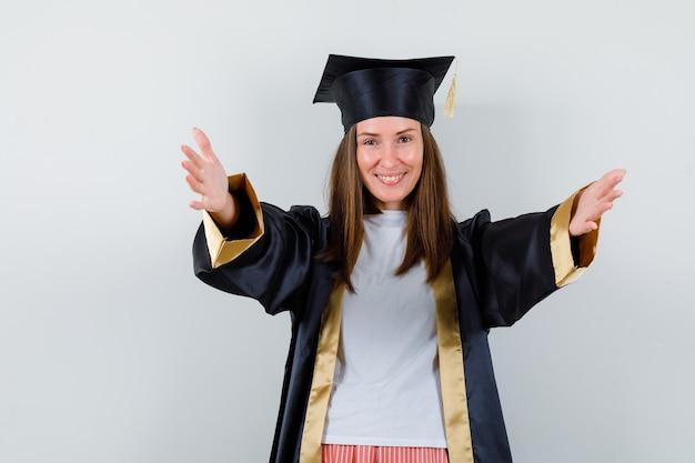 Ritratto di donna laureata che apre le braccia per abbraccio in uniforme, abbigliamento casual e che sembra felice vista frontale