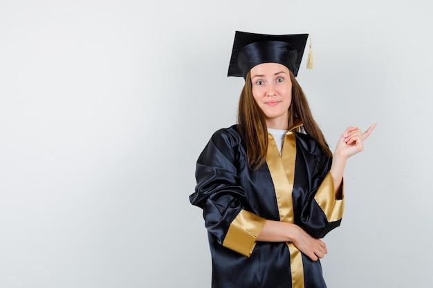 Ritratto di donna laureata che punta all'angolo in alto a destra in abito accademico e guardando fiducioso vista frontale
