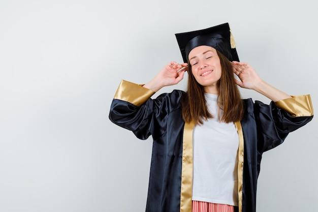 Ritratto di donna laureata in posa mentre levandosi in piedi in abito accademico e guardando vista frontale rilassata