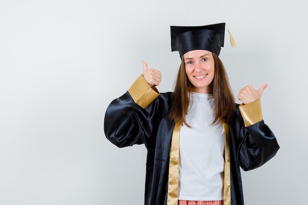 Ritratto di donna laureata che mostra il doppio pollice in alto in uniforme, abbigliamento casual e guardando fortunato vista frontale